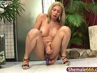 Crazy blonde shemale riding a huge dildo