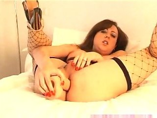 Burning TS in fishnet stockings plays with a dildo