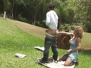 Blonde shemale fucks guy doggy style in a park