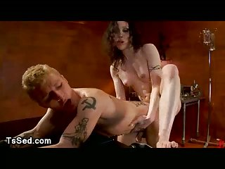 Brunette tranny fucks blonde strapped guy in his ass and throat