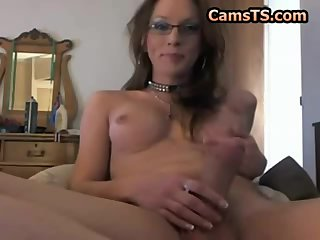Tgirl in glasses strokes her big dick to a climax