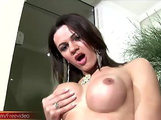 Brunette shemale in lingerie and stockings flashes big tits